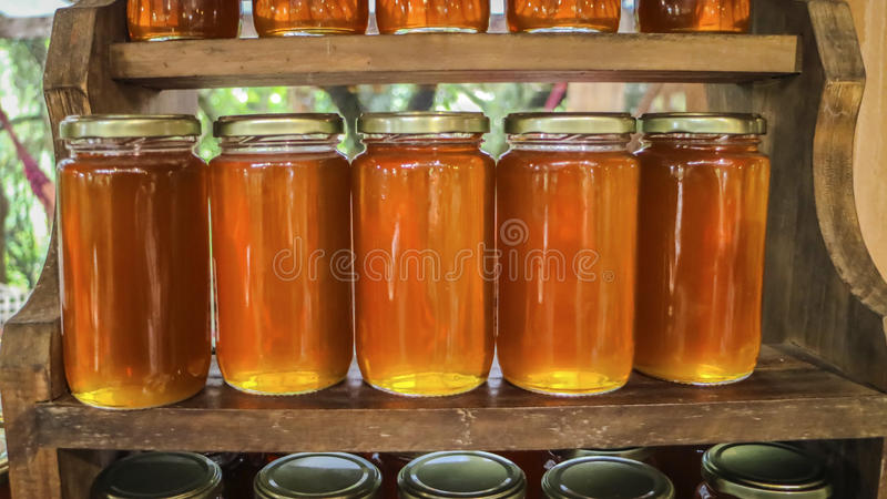 Flowery κίτρινο μέλι στο βάζο γυαλιού στοκ εικόνες