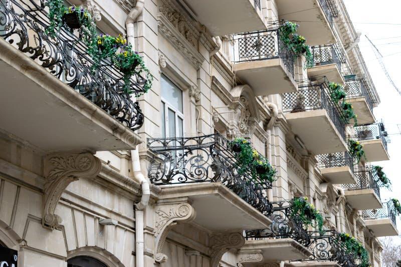 Flowery μπαλκόνι σε μια οδό πόλεων Flowerpots και εγκαταστάσεις σπιτιών στο μπαλκόνι Κλασικό μπαλκόνι ύφους με τα λουλούδια στοκ εικόνα με δικαίωμα ελεύθερης χρήσης