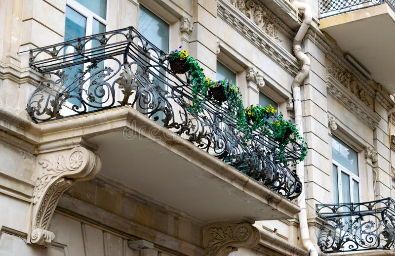 Flowery balcony in a city street. Flowerpots and house plants on the balcony. Classic style balcony with flowers royalty free stock photo