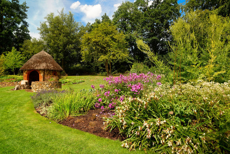 Flowery english garden scene with small hut stock photo for Small garden huts