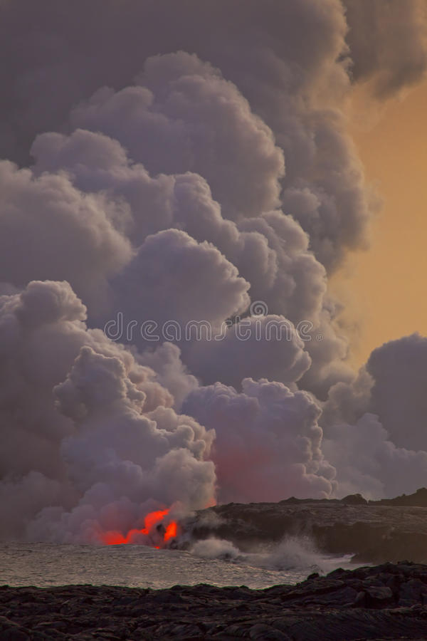 Flowing lava into the ocean royalty free stock image