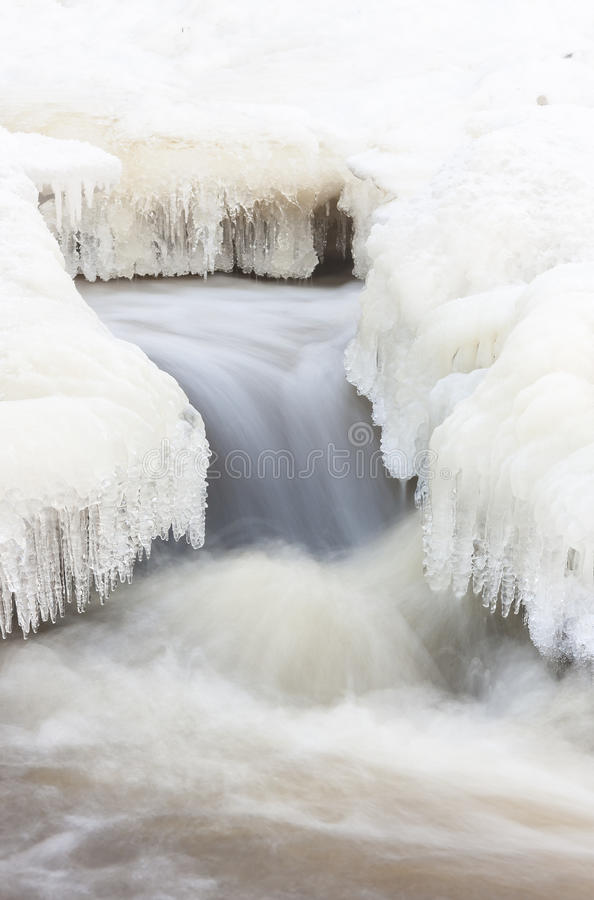 Flowing river and icicles in winter stock photo