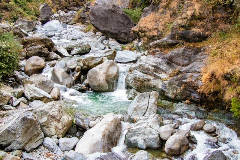 Flowing stream through green mossy rocks in forest, royalty free stock image