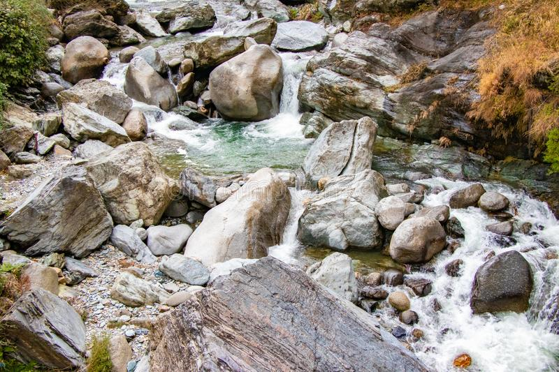 Flowing stream through green mossy rocks in forest, royalty free stock photography
