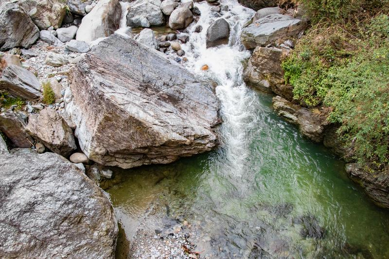 Flowing stream through green mossy rocks in forest, royalty free stock images