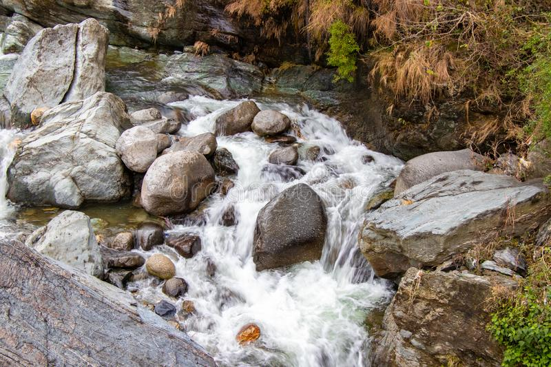 Flowing stream through green mossy rocks in forest, stock photography