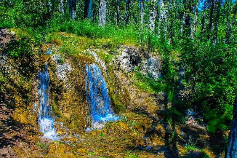 Flowing water, Big Hill Springs Provincial Recreation Area, Alberta, Canada. Water cascades down a rock formation at the lower end of the springs during the stock images