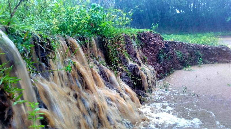 Flowing water causing soil erosion during heavy rain and flood. Mud and flowing water reach a pond / swamp during heavy rain looks like water fall causing soil stock image