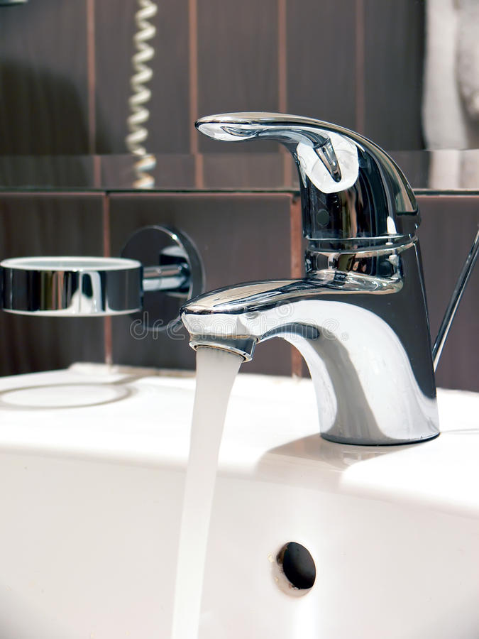 Flowing water faucet stock image