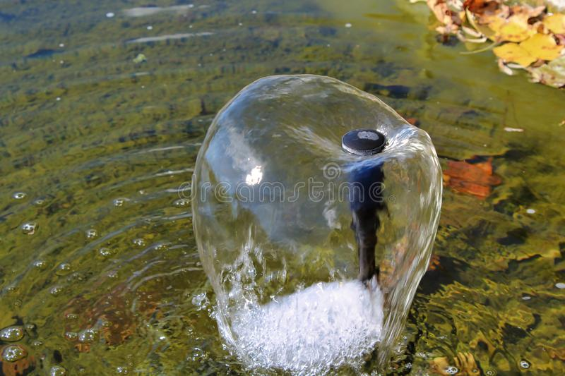 Flowing water from a sprinkler fountain forming a bubble on a small backyard pond. Shimmering water coming from a sprinkler fountain head forming a cone in a royalty free stock image