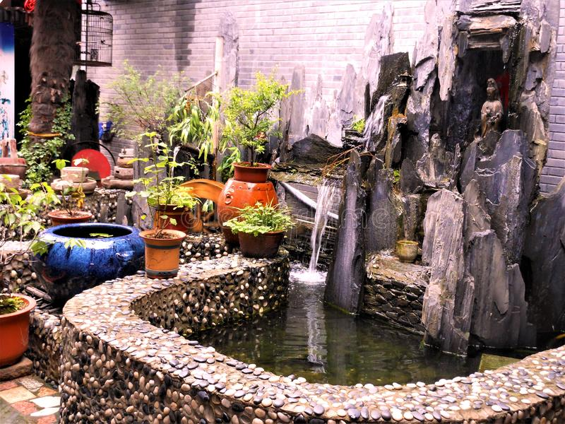 Flowing water, stones, fountain, vases, plants, bird cage, peace and relax in China. Flowing water, stones, fountain, vases, plants, bird cage, peace and relax stock photography