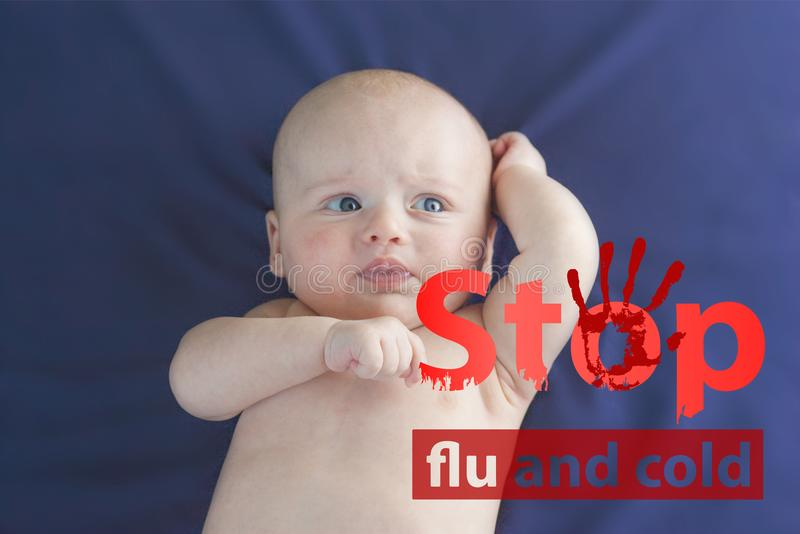 Flu and cold. crying baby. Little child on a blue sheet stock photo