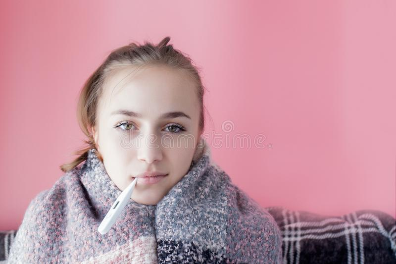 Flu cold grippe. Woman having high temperature. Sick girl with fever checking mercury thermometer on pink background stock photos