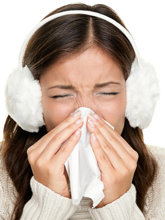 Flu or cold sneezing woman. Flu or cold - sneezing woman sick blowing nose. Young woman being cold wearing earmuffs and sweater. Asian Caucasian female model stock photos