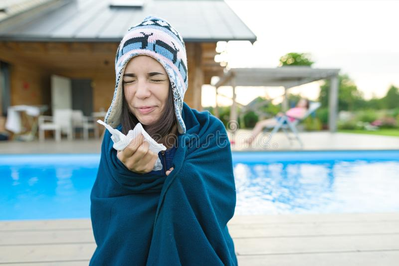 Flu, colds in the summer. Girl in a knitted hat with plaid with handkerchief sneezes, wipes her nose. Background nature, pool, gir. L in chaise longue stock photos