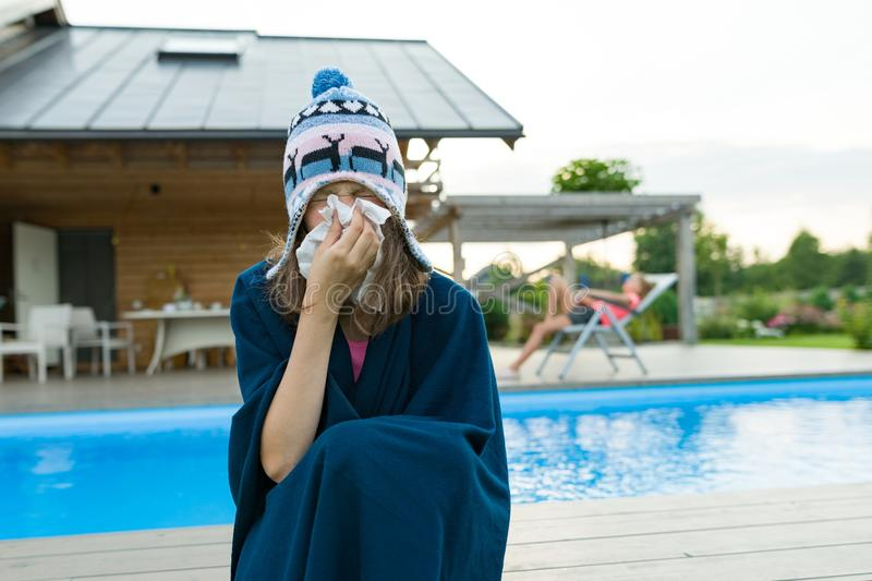 Flu, colds in the summer. Girl in a knitted hat with plaid with handkerchief sneezes, wipes her nose. Background nature, pool, gir. Lfriend in chaise longue stock image