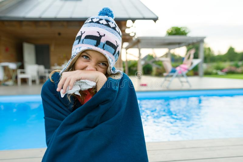 Flu, colds in the summer. Girl in a knitted hat with plaid with handkerchief sneezes, wipes her nose. Background nature, pool, gir. Lfriend in chaise longue stock images