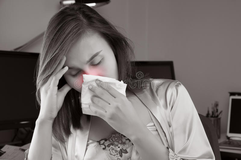 Flu and Headache. Asian woman in satin nightwear feeling unwell and sneeze on desk at home. People Caught Cold and flu stock image