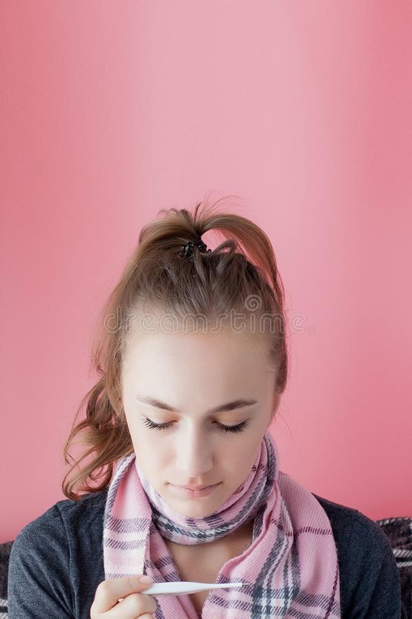Flu kallt galler Kvinnor med hög temperatur Sjuk flicka med feber som kontrollerar kvicksilvertermometer på rosa bakgrund arkivbilder