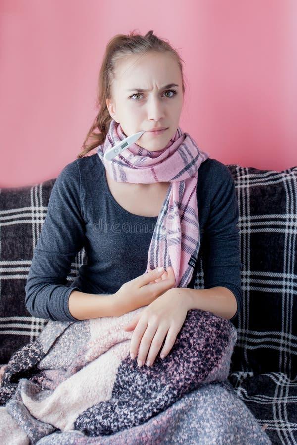 Flu kallt galler Kvinnor med hög temperatur Sjuk flicka med feber som kontrollerar kvicksilvertermometer på rosa bakgrund royaltyfria bilder