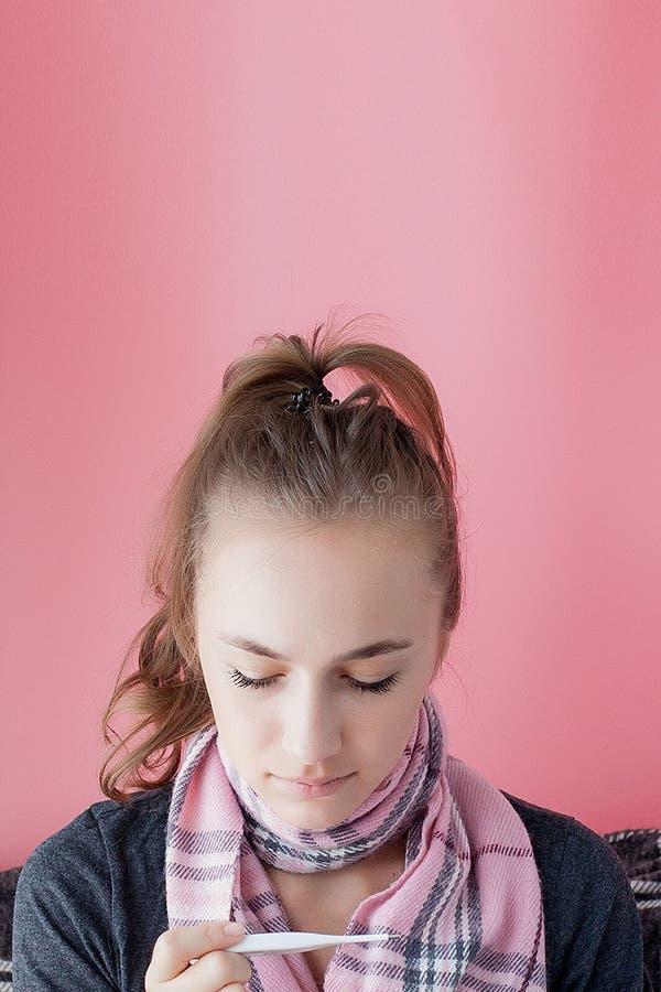 Flu kallt galler Kvinnor med hög temperatur Sjuk flicka med feber som kontrollerar kvicksilvertermometer på rosa bakgrund royaltyfri bild