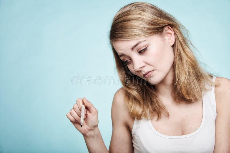 flu Menina doente com febre que verifica o termômetro fotos de stock