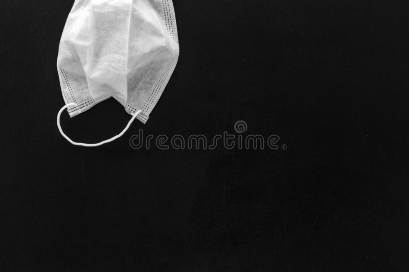 Flu prevention concept. Medical face mask on black background top view copy space. Flu prevention concept. Medical face mask on black background top view royalty free stock photo