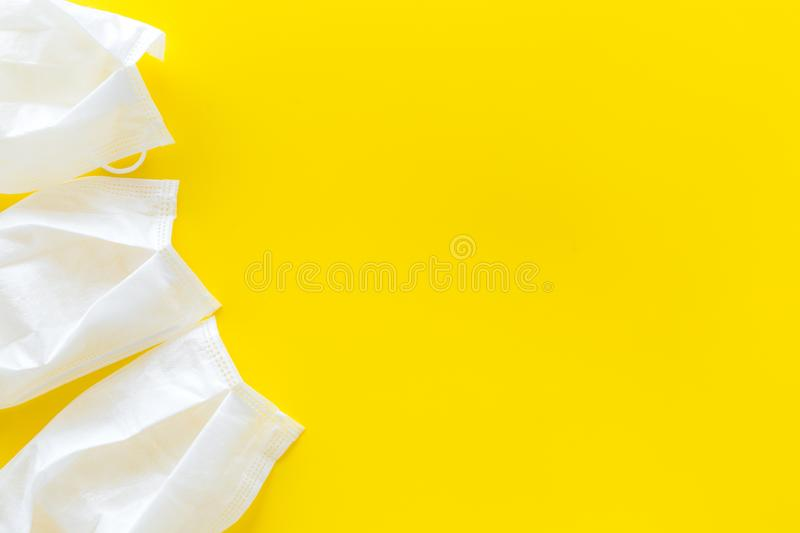Flu prevention concept. Medical face mask on yellow background top view copy space frame. Flu prevention concept. Medical face mask on yellow background top view royalty free stock photography