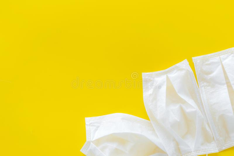 Flu prevention concept. Medical face mask on yellow background top view copy space frame. Flu prevention concept. Medical face mask on yellow background top view stock images
