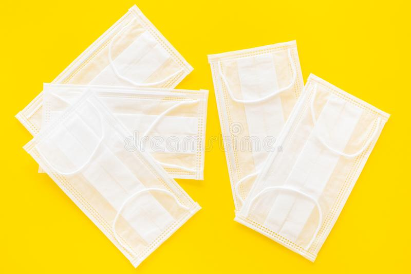 Flu prevention. Medical face masks on yellow background top view.  royalty free stock photography