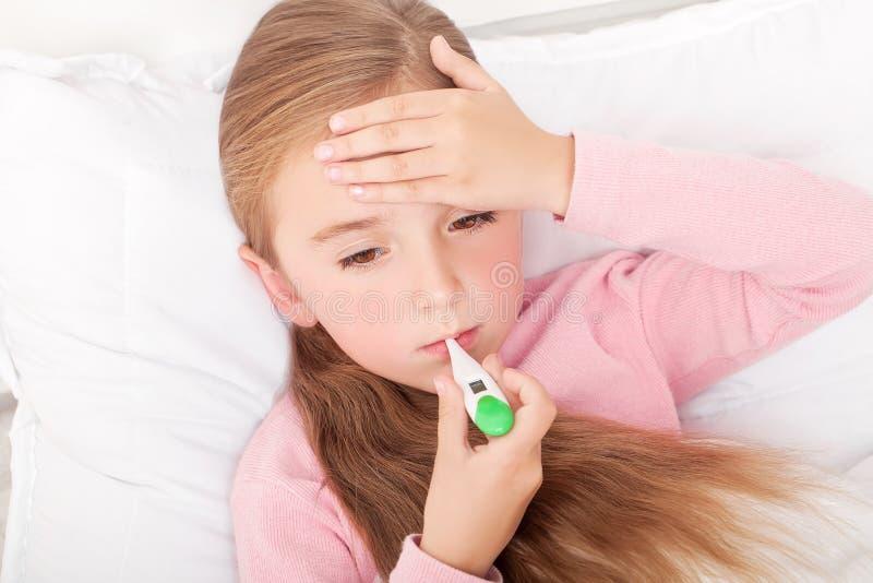 flu Ragazza che si trova a letto con un termometro fotografie stock libere da diritti