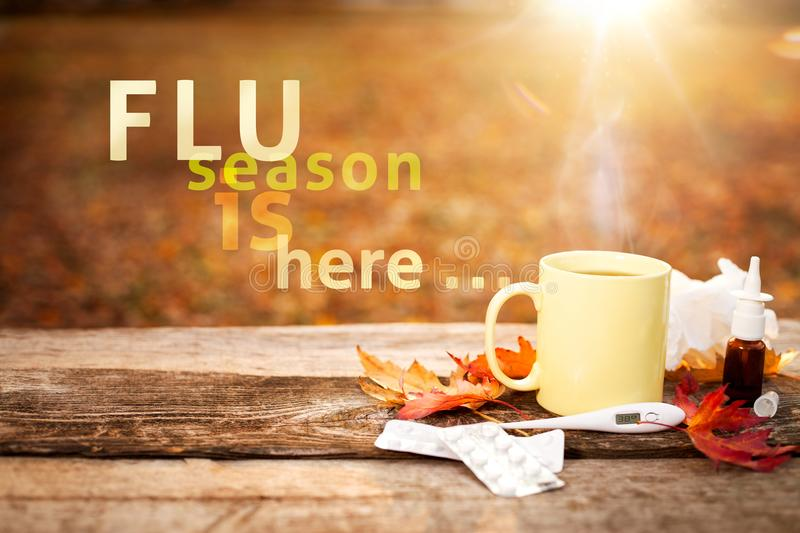 Flu season in autumn. Tea cup, thermometer, autumn leaves and nose drops on wooden surface, flu season in autumn royalty free stock photography
