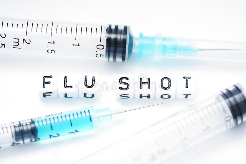 Flu shot text spelled with tiled letters standing next to a syringe royalty free stock image