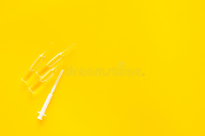 Flu vaccination concept. Syringe and ampoulie on yellow background top view copy space. Flu vaccination concept. Syringe and ampoulie on yellow background top royalty free stock photo