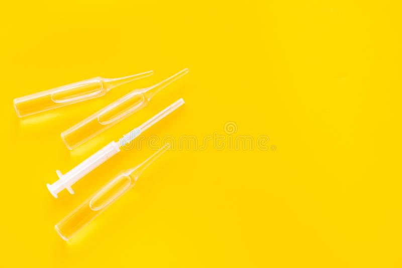 Flu vaccination concept. Syringe and ampoulie on yellow background top view copy space. Flu vaccination concept. Syringe and ampoulie on yellow background top stock photo
