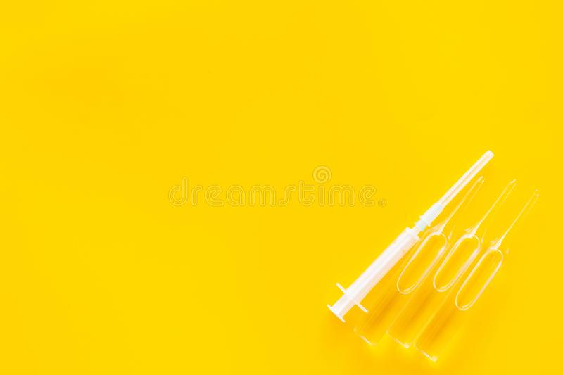 Flu vaccination concept. Syringe and ampoulie on yellow background top view copy space. Flu vaccination concept. Syringe and ampoulie on yellow background top royalty free stock photography