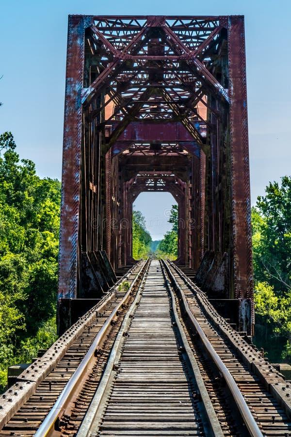 Fluchtpunkt-Ansicht eines alten Eisenbahn-Gestells mit einer alten Eisen-Fachwerkbrücke über dem Brazos River stockbild