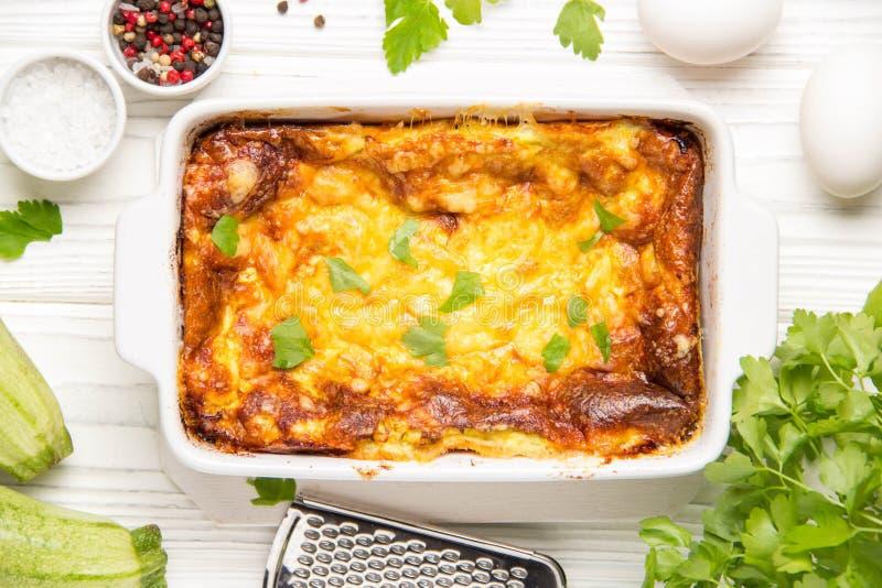 Fluffig omelett som bakas med zucchinin, sund frukost för ungar, smaklig eldfast form På vit träbakgrund i att baka maträtten royaltyfri fotografi