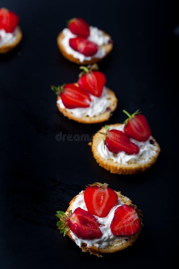Fluffig shortcake för kärnmjölkkex med röda mogna jordgubbar och ny piskad kräm på en svart bakgrund arkivfoto