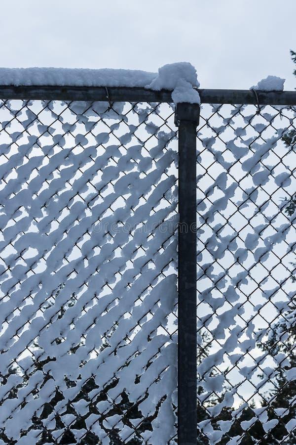 Fluffig vit snö som samlas i ett staket för kedjesammanlänkning royaltyfri foto