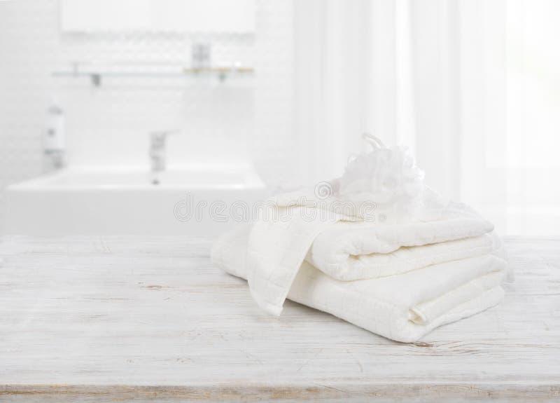 Fluffiga handdukar och test av bast över suddig badrumbakgrund arkivfoton