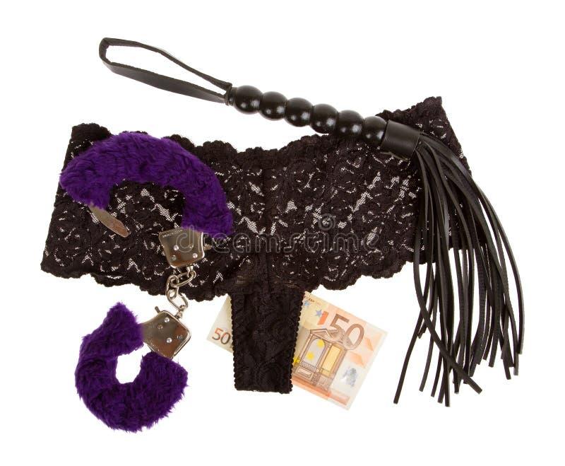 Fluffiga lilahandbojor, en piska, pengar och underbyxor, prostitution arkivfoton