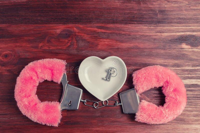 Fluffiga rosa färghandbojor och ett keramiskt tefat i formen av en hjärta, där lögn tangenterna arkivfoton