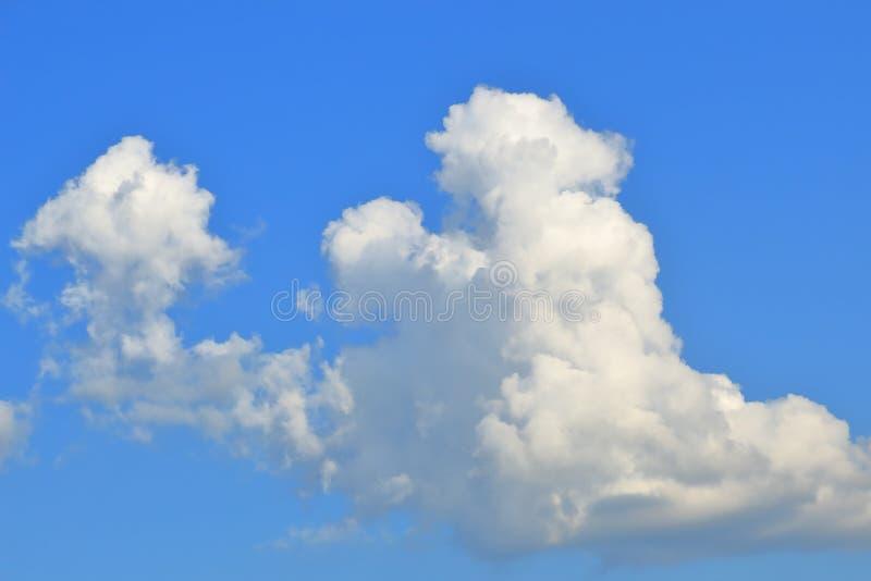 Fluffiga vita stackmolnmoln på en bakgrund för djupblå himmel royaltyfri bild