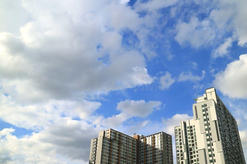 Fluffiga vitmoln och vibrerande blå himmel över de höga byggnaderna i Bangkok arkivbild