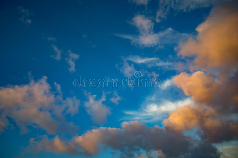 Fluffy big sunset clouds and blue royalty free stock photography