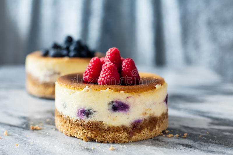 Cheesecake. This fluffy cheesecake is filled with blueberries inside with crumbly graham cracker crust. Topped with fresh raspberry and blueberry. This dessert royalty free stock photos