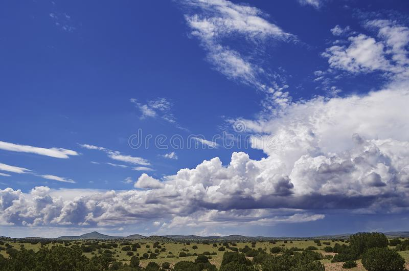 Fluffy clouds dance over the southwest landscape of north central New Mexico after a recent rain shower.  stock images