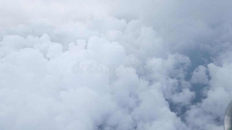 Fluffy clouds in the sky. View from the plane window. In the corner is visible part of the aircraft royalty free stock photos