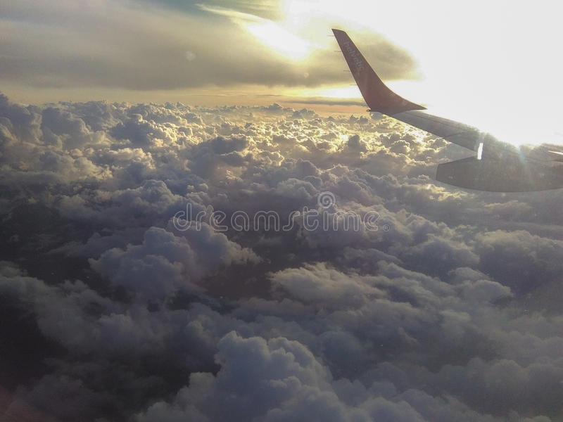 Fluffy clouds, sun and aircraft wing. Aerial view. royalty free stock photos